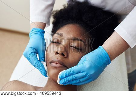 Skin Cleansing With Cotton Pads In The Beauticians Office. A Dark-skinned Young Woman Lies On Proced