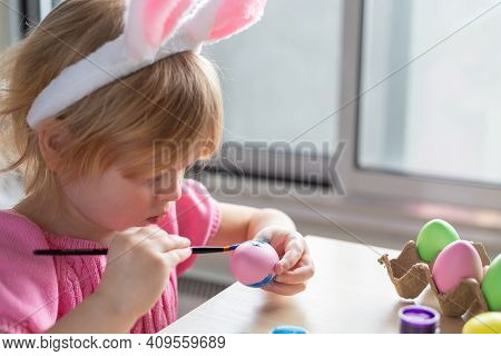 Little Girl In Easter Bunny Ears Painting Colored Eggs. Easter Family Holiday Celebration At Home An