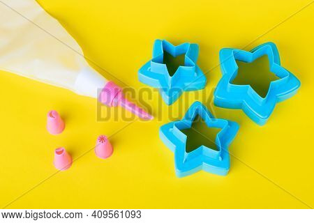 Star Shaped Cookie Cutters. Cake Decorating Tools, Pastry Bag With Nozzles On A Yellow Background Fo