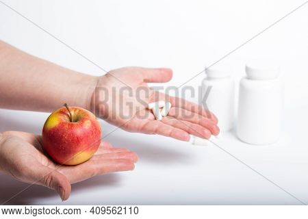 One Hand Holding Red Aple, And Other One Capsules With Vitamines.