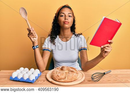 Young african american girl making homemade bread holding spoon and book recipe relaxed with serious expression on face. simple and natural looking at the camera.
