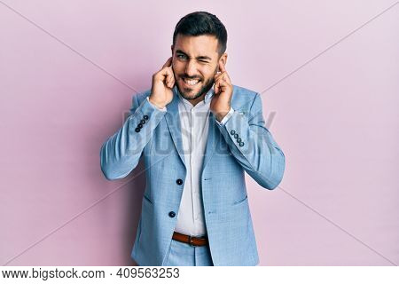 Young hispanic businessman wearing business jacket covering ears with fingers with annoyed expression for the noise of loud music. deaf concept.