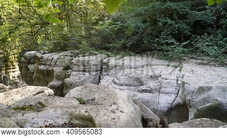 Waterfall In A Crevice Between The Rocks Behind The Trees. Canyons Of The Khosta River. White Rocks