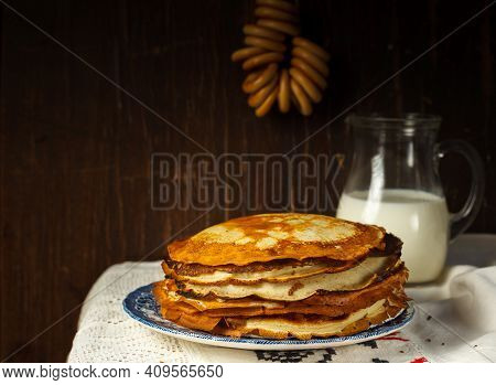 Pancake Day. Thin Pancakes Stacked On A Painted Plate, On A Linen Embroidered Tablecloth. Dark Woode