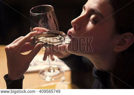 Portrait Of A Young Woman Having Lunch With Mussels And Wine. Seafood And Mediterranean Cuisine With