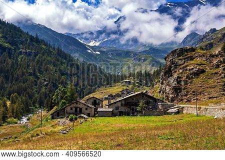 Small alpine village in the valley among mountains in Piedmont, Northern Italy.