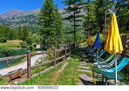 Deckchairs and umbrellas along small alpine lake Laux among green tree in Piedmont, Northern Italy.