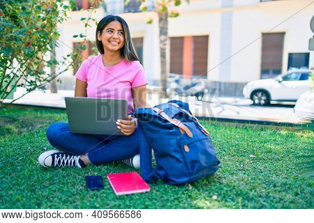Young latin student girl smiling happy using laptop at university campus