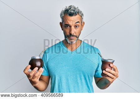 Middle age grey-haired man drinking mate infusion skeptic and nervous, frowning upset because of problem. negative person.