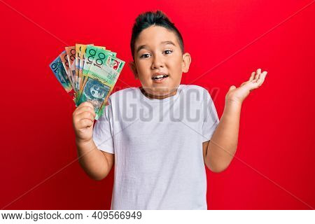 Little boy hispanic kid holding australian dollars celebrating achievement with happy smile and winner expression with raised hand