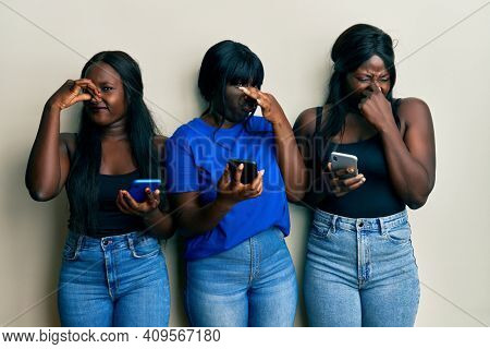 Three young african american friends using smartphone smelling something stinky and disgusting, intolerable smell, holding breath with fingers on nose. bad smell