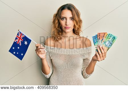 Young caucasian woman holding australian flag and dollars relaxed with serious expression on face. simple and natural looking at the camera.