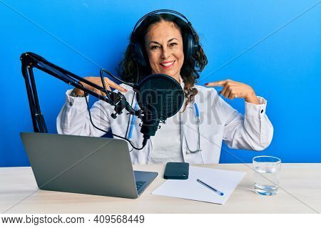 Beautiful middle age doctor woman working at radio studio looking confident with smile on face, pointing oneself with fingers proud and happy.