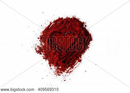 Close-up Of Ground Red Chili Pepper Over White Background. Pile Of Ground Paprika Isolated In Heart