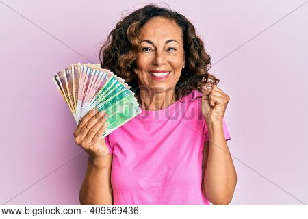 Middle age hispanic woman holding norwegian krone banknotes screaming proud, celebrating victory and success very excited with raised arm
