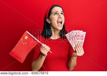 Young hispanic woman holding china flag and yuan banknotes angry and mad screaming frustrated and furious, shouting with anger looking up.
