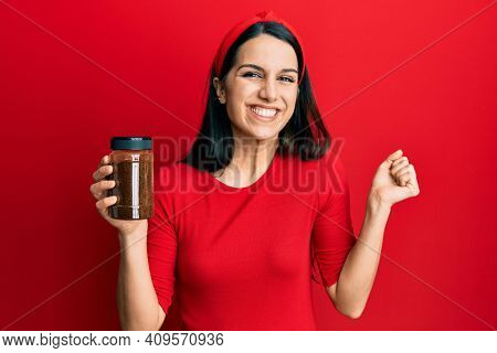 Young hispanic woman holding soluble coffee screaming proud, celebrating victory and success very excited with raised arm