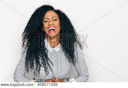 Middle age african american woman wearing casual clothes smiling and laughing hard out loud because funny crazy joke with hands on body.