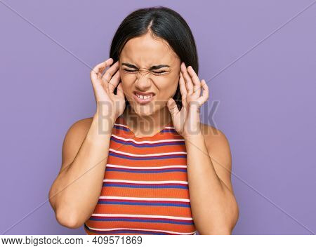 Young brunette woman wearing casual clothes covering ears with fingers with annoyed expression for the noise of loud music. deaf concept.