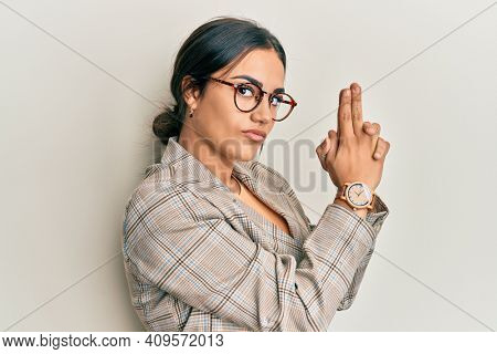 Young brunette woman wearing business jacket and glasses holding symbolic gun with hand gesture, playing killing shooting weapons, angry face