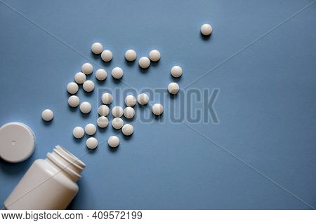 Bottle And Scattered White Round Pills On Blue Background, Top View, Flat Lay. Medical Theme, Space