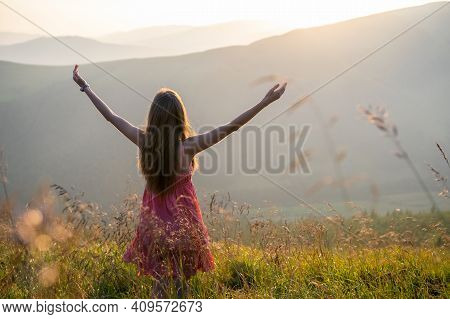 Back View Of Young Happy Woman Traveler In Red Dress Standing On Grassy Hillside On A Windy Evening