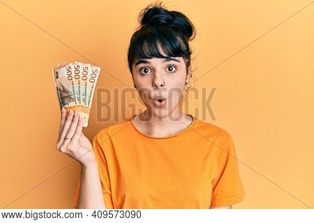 Young hispanic girl holding norwegian krone banknotes scared and amazed with open mouth for surprise, disbelief face