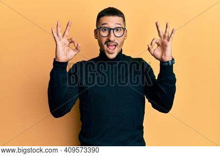 Handsome man with tattoos wearing turtleneck sweater and glasses looking surprised and shocked doing ok approval symbol with fingers. crazy expression