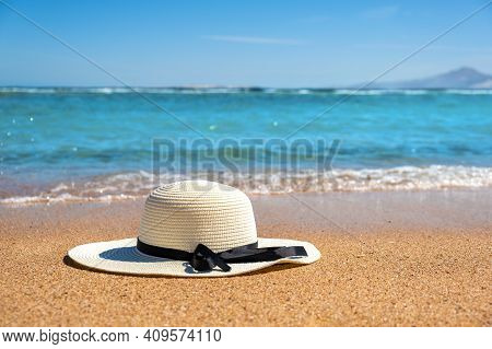 White Woman Straw Hat Laying On Tropical Sand Beach With Blue Vibrant Ocean Water In Background On S