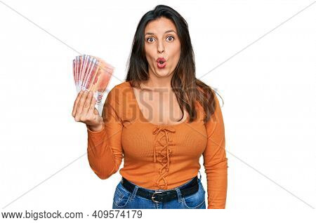 Beautiful hispanic woman holding norwegian krone banknotes scared and amazed with open mouth for surprise, disbelief face