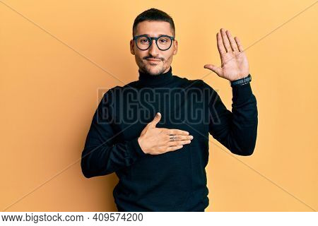 Handsome man with tattoos wearing turtleneck sweater and glasses swearing with hand on chest and open palm, making a loyalty promise oath
