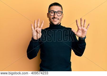 Handsome man with tattoos wearing turtleneck sweater and glasses showing and pointing up with fingers number nine while smiling confident and happy.