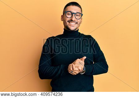 Handsome man with tattoos wearing turtleneck sweater and glasses with hands together and crossed fingers smiling relaxed and cheerful. success and optimistic