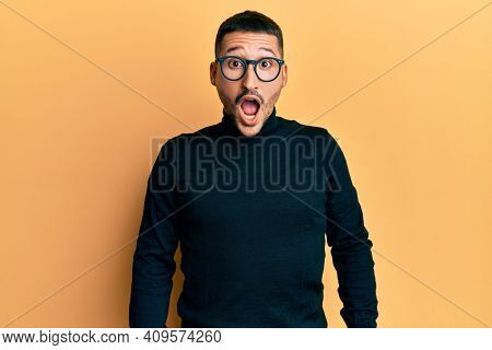 Handsome man with tattoos wearing turtleneck sweater and glasses afraid and shocked with surprise and amazed expression, fear and excited face.
