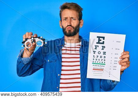 Handsome caucasian man with beard holding optometry glasses and eyesight test looking at the camera blowing a kiss being lovely and sexy. love expression.