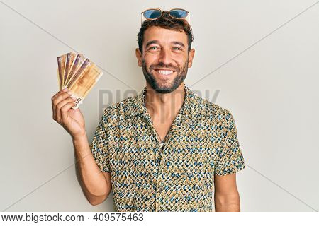 Handsome man with beard holding 500 norwegian krone banknotes looking positive and happy standing and smiling with a confident smile showing teeth