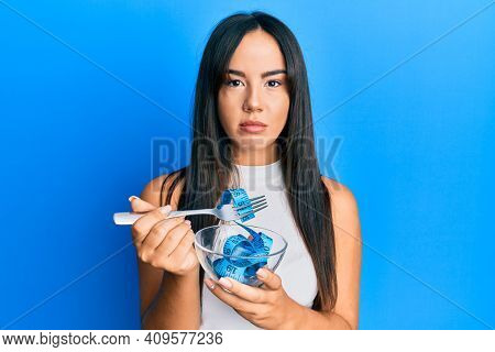Young beautiful hispanic girl eating measure meter doing diet for weight loss relaxed with serious expression on face. simple and natural looking at the camera.