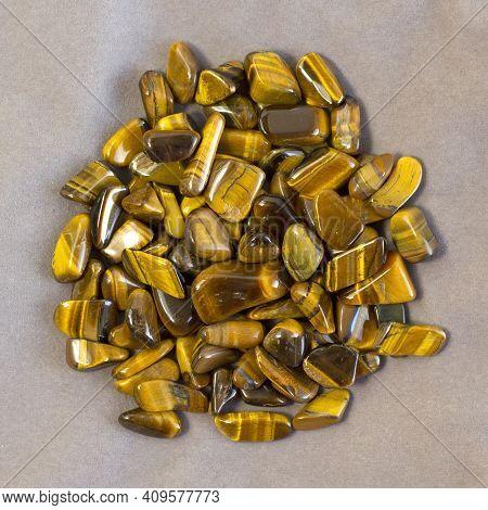 Natural Mineral Gem Stone Tigers Eye Tigers Eye, Tiger Eye Gemstoneon On Light Beige Background Clos