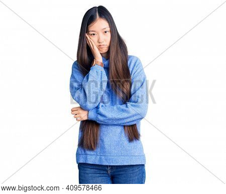 Young beautiful chinese woman wearing casual turtleneck sweater thinking looking tired and bored with depression problems with crossed arms.