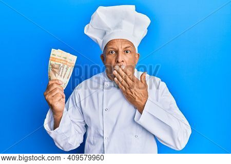 Middle age grey-haired man wearing professional cook uniform holding norwegian krona banknotes covering mouth with hand, shocked and afraid for mistake. surprised expression
