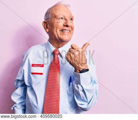 Senior handsome grey-haired businessman wearing tie and shirt with name presentation sticker pointing thumb up to the side smiling happy with open mouth