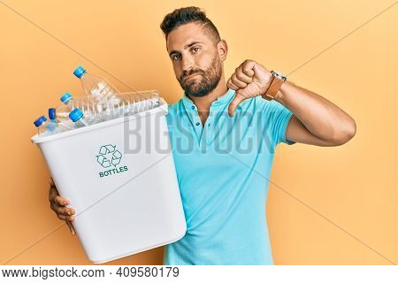 Handsome man with beard holding recycling wastebasket with plastic bottles with angry face, negative sign showing dislike with thumbs down, rejection concept