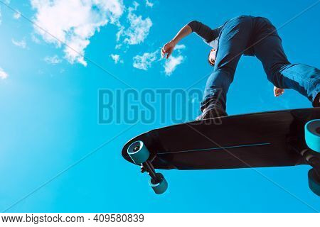 Skater In Action. Man Making A Trick On A Longboard Outdoors On Sunny Summer Day. Blue Sky Backgroun