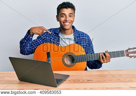 Young handsome african american man learning classical guitar from online tutorial pointing finger to one self smiling happy and proud