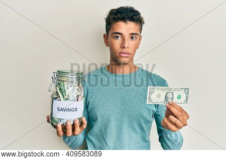Young handsome african american man holding jar with savings relaxed with serious expression on face. simple and natural looking at the camera.