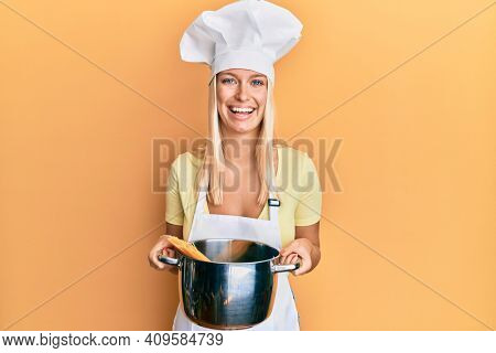 Young blonde girl cooking spaghetti smiling and laughing hard out loud because funny crazy joke.