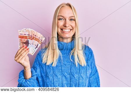 Young blonde girl holding 100 norwegian krone banknotes looking positive and happy standing and smiling with a confident smile showing teeth