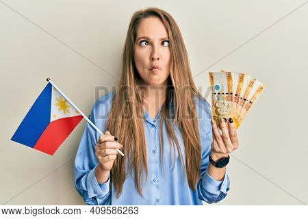Young blonde woman holding philippine flag and philippines pesos banknotes making fish face with mouth and squinting eyes, crazy and comical.