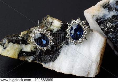 Silver Earrings With Blue Stone On Natural Stone. Bijouterie Earrings Close Up