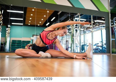 Beautiful Slim Athletic Woman In The Sportswear Doing Fitness Stretching Exercises In The Gym. Athle
